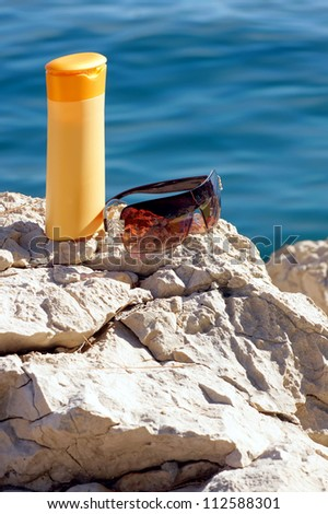 Sun protection- sunscreen and sunglasses on a rock by the sea.