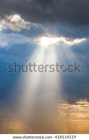 sun ray light through down from rain cloud during sunset time - stock photo