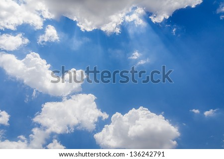 Sun ray shining through the clouds in the blue sky