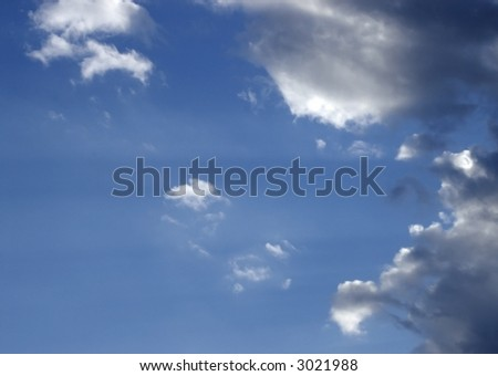 Sun rays and clouds against  blue sky - stock photo