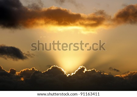 Sun rays and dark clouds at sunset - stock photo