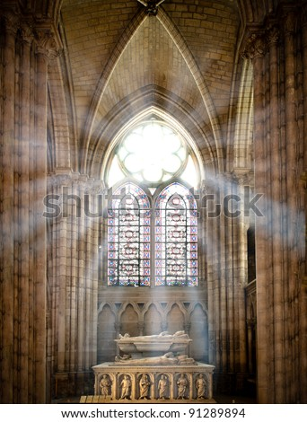 sun rays beaming through the old stained glass window of saint denis cathedral and lighting interior with tomb. Paris, France, Europe. - stock photo