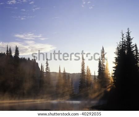 Sun rays break through the morning mist on Reflection Lake in Mt Rainier National Park, Washington. - stock photo
