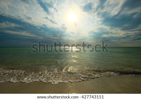 sun rays breaking through clouds above a silent sea
