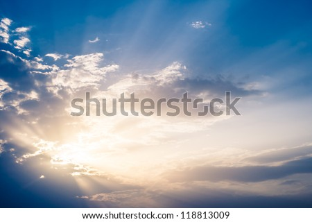 Sun rays bursting through the clouds. - stock photo