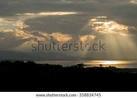 Sun rays during sunrise over the moutain and lake, Thailand - stock photo