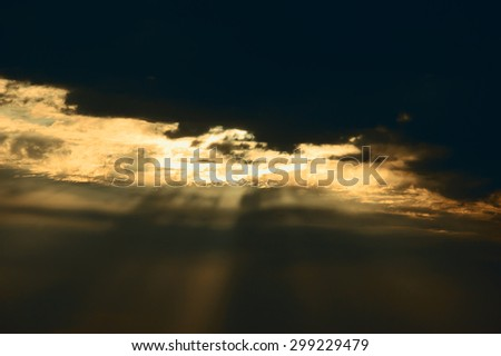 Sun rays glowing through the clouds. Dramatic lighting before a storm. Apocalypse concept. - stock photo