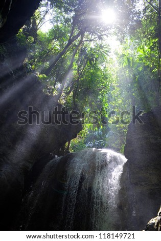 Sun rays in a cave with falls. Jamaica - stock photo