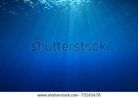Sun rays in blue ocean - stock photo