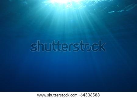 Sun rays in blue water - stock photo