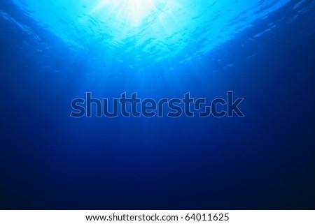 Sun rays in the blue sea - stock photo