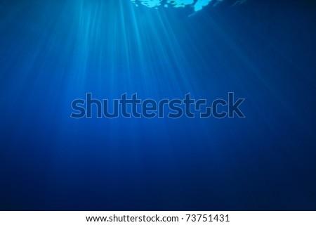 Sun rays in the ocean - stock photo
