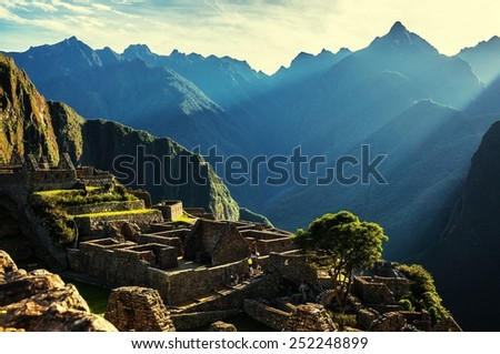 Sun rays of light shining at the ruins of Machu Picchu, Peru. Machu Picchu at sunrise when the sunlight makes everything golden-warm. Sacred Valley. - stock photo