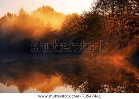 Sun rays pass through the mist on the lake - stock photo