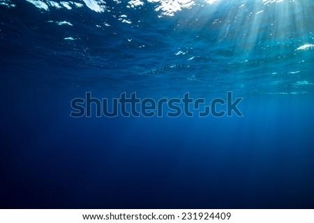 Sun rays penetrating water column - stock photo