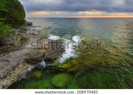 Sun rays shine through clouds over Lake Michigan at Door County, Wisconsin's Cave Point. - stock photo