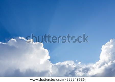 Sun rays shining behind cloud in the sky - stock photo