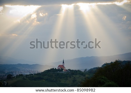 Sun rays shining down on a Church - stock photo
