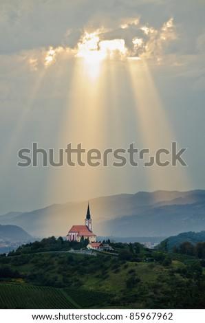 Sun rays shining down on a Church - stock photo