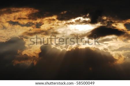 Sun rays shining through the storm cloud - stock photo