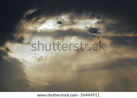 Sun rays shining through the stormy cloud - stock photo