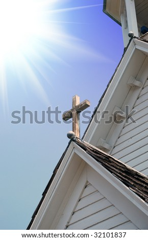 Sun rays shining up from wood  cross on a small  old Christian orthodox Church. - stock photo
