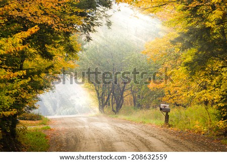 Sun rays streaking through trees onto a mailbox on a pole on the side of a dirt road during fall foliage in Stowe, Vermont, USA - stock photo