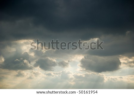 Sun rays streaming trough an opening of the clouds - stock photo