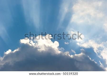 Sun rays streaming trough the clouds - stock photo