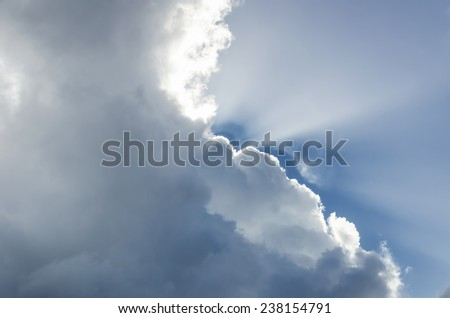 Sun rays striking through clouds - stock photo