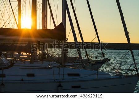 sun rays through boat masts at sunset