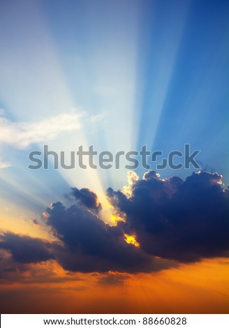 Sun rays through clouds at sunset