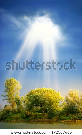Sun rays through clouds shine meadow with  trees - stock photo