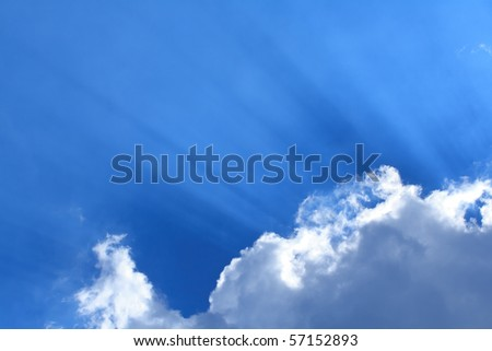 Sun rays with the blue cloudy sky in the background - stock photo