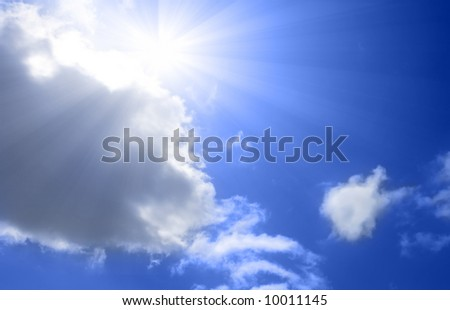 Sun reappearing from behind clouds on brilliant blue sky - stock photo