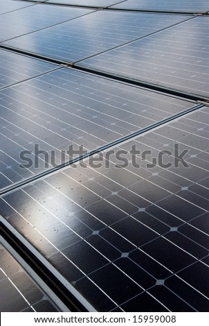 Sun reflecting on roof mounted solar energy panels - stock photo