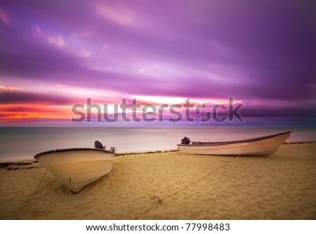 Sun rise on violet sky with boat - stock photo