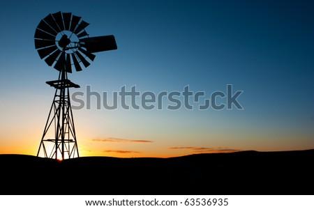 Sun rises behind a windmill - stock photo