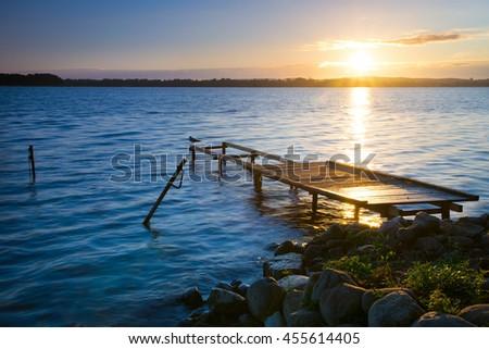 Sun rises over empty footbridge and moored boats. Lasmiady lake, Masuria, Poland - stock photo