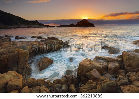 Sun rising behind Mimosa Rocks, the geology here is varied and includes various volcanics, mixed with mudstone, interesting sea stacks and columnar jointing. - stock photo