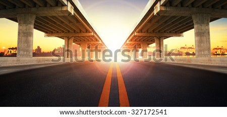 sun rising behind perspective on bridge ram construction and asphalt road perspective to ship port background use for infra land and vessel transportation - stock photo