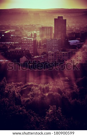 Sun rising from behind a hill over a part of large city - stock photo