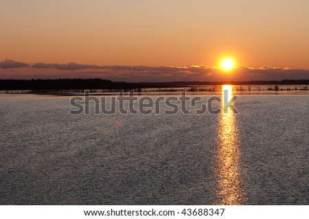 sun rising over a lake in the forrest - stock photo