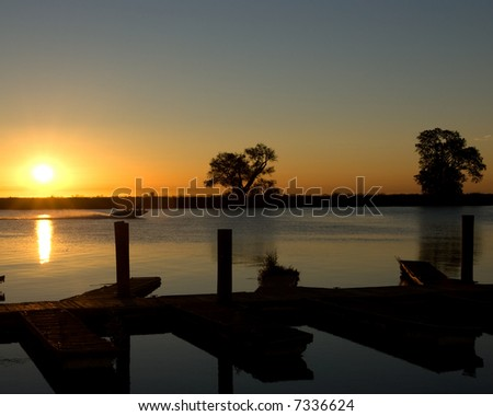 Sun rising over delta waters with ski boat racing across the water, docks in the foreground and oak trees in the background. - stock photo
