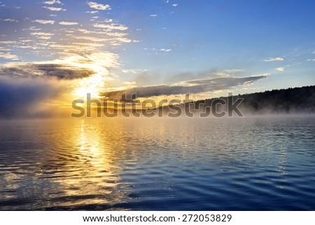 Sun rising over foggy lake in Algonquin Park, Canada - stock photo