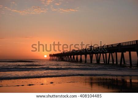 Sun rising over horizon and pier, beach illuminated with sunlight, Jacksonville Florida, USA. - stock photo