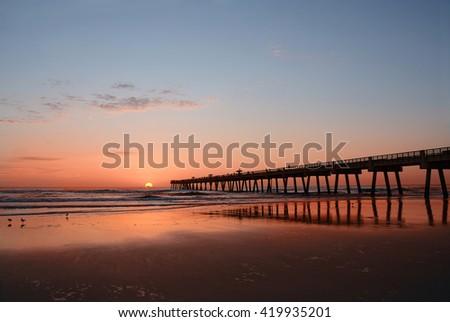 Sun rising over horizon and pier, beach illuminated with sunlight.  Jacksonville Florida, USA. - stock photo