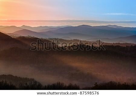 Sun rising over snowy mountains of Smokies in early spring with fog in the valleys - stock photo