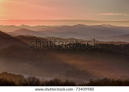 Sun rising over snowy mountains of Smokies in early spring with fog in valleys - stock photo