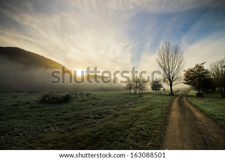Sun rising up with early morning mist around mountains, Hastings, New Zealand - stock photo